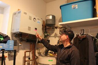 Philip Richards points to his electric boiler. (Photo by Elizabeth Jenkins/Alaska's Energy Desk)