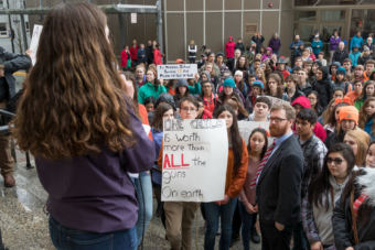 Katie McKenna speaks on the steps of the Alaska State Capitol building in Juneau at a student walkout protest on Wednesday, March 14, 2018. Students and Juneau Rep. Justin Parish, wearing the coat and tie, listen.
