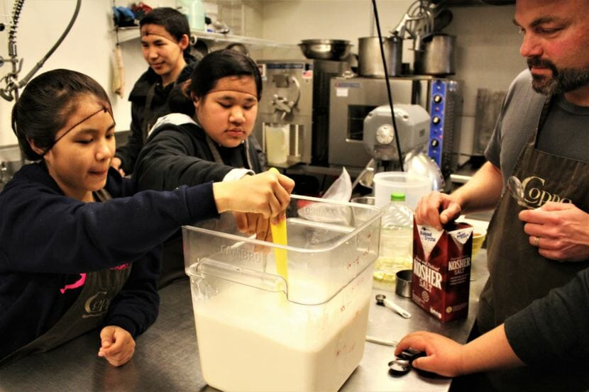 Students on a cultural exchange trip from Noorvik Aqqaluk School make ice cream with Marc Wheeler in the kitchen at Coppa in Juneau. (Photo by Adelyn Baxter/KTOO)
