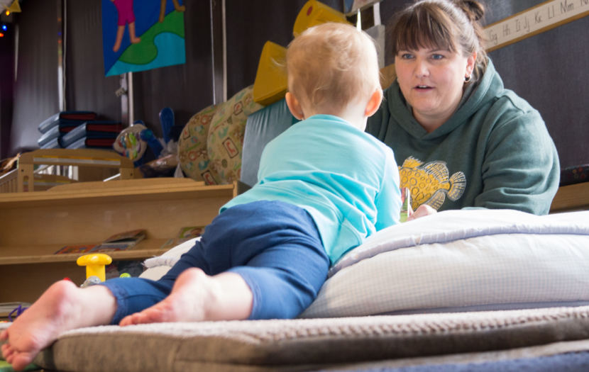 Gretchen Boone flips through a picture book for an infant at the Gold Creek Child Development Center in Juneau on May 11, 2018. Boone is the center's director.