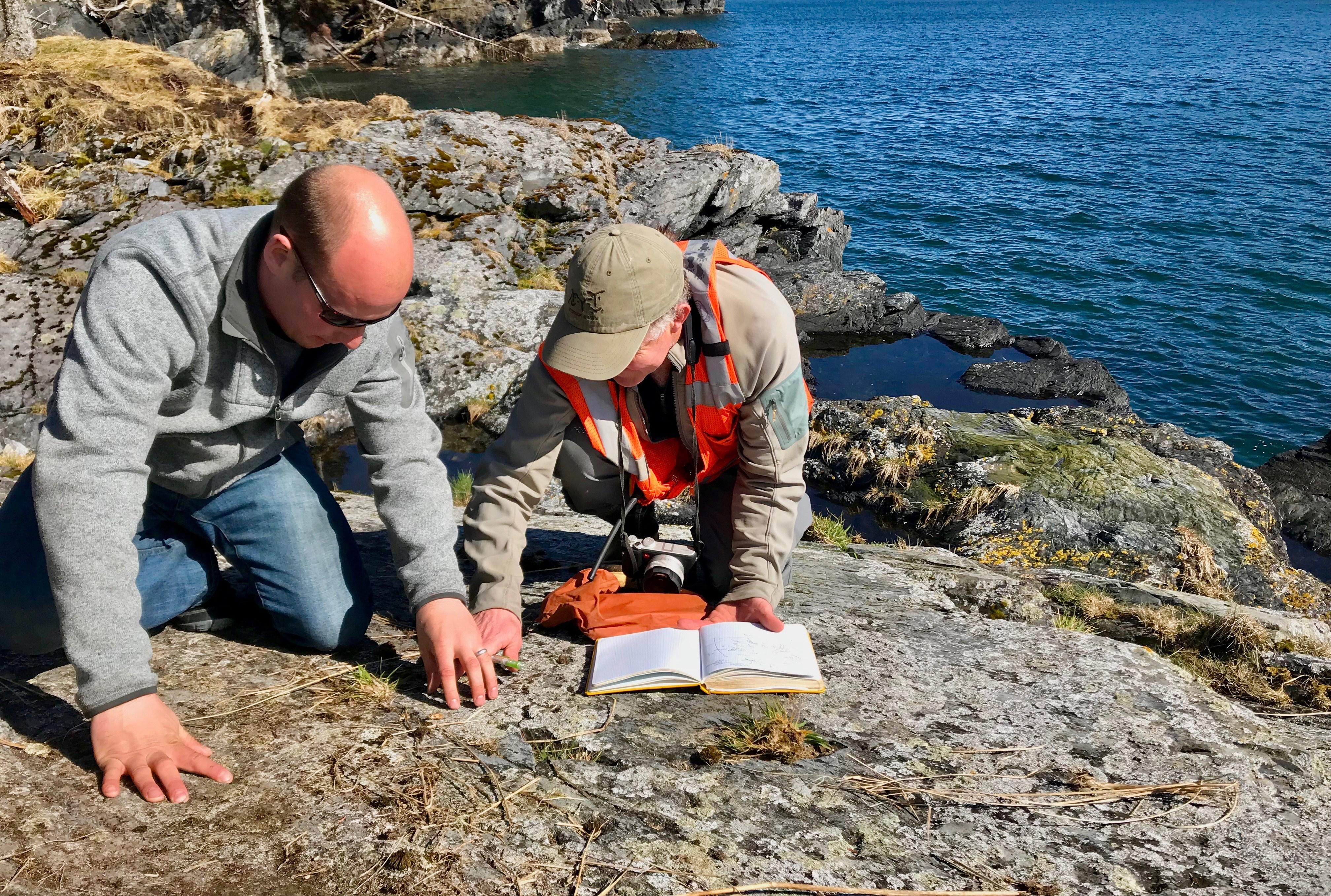 Museum archaeologist Patrick Saltonstall and helicopter pilot Keller Wattum document a petroglyph site on Afognak. (Photo courtesy Patrick Saltonstall)