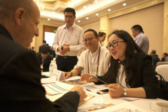 """Ron Risher of Icicle Seafoods talk to Crescent Xuan, Manager of International Trade for the Sichuan Jinggong Flavor Co., during a """"speed dating"""" event designed to bring companies with Alaska products to Chinese consumers on Tuesday, May 22, 2018, in Chengdu, China. (Photo by Rashah McChesney/Alaska's Energy Desk)"""