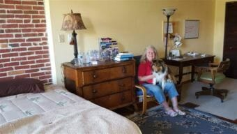 Baltimore resident Jeannette Belliveau, who rents a couple of rooms in her historic townhouse to short-term guests, sits with her dog, Copper, in one of the guest suites. States are having a hard time regulating the short-term rental industry. (Photo by Pew Charitable Trusts)