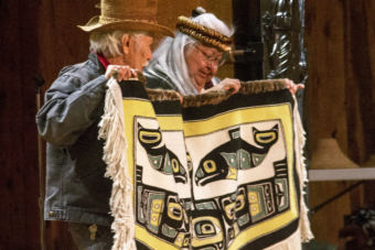 Nathan Jackson, left, and Della Cheney hold up a blanket made by Dorica Jackson during a weavers' presentation at the Shuka Hit clan house at the Walter Soboleff Building in downtown Juneau on June 6, 2018.