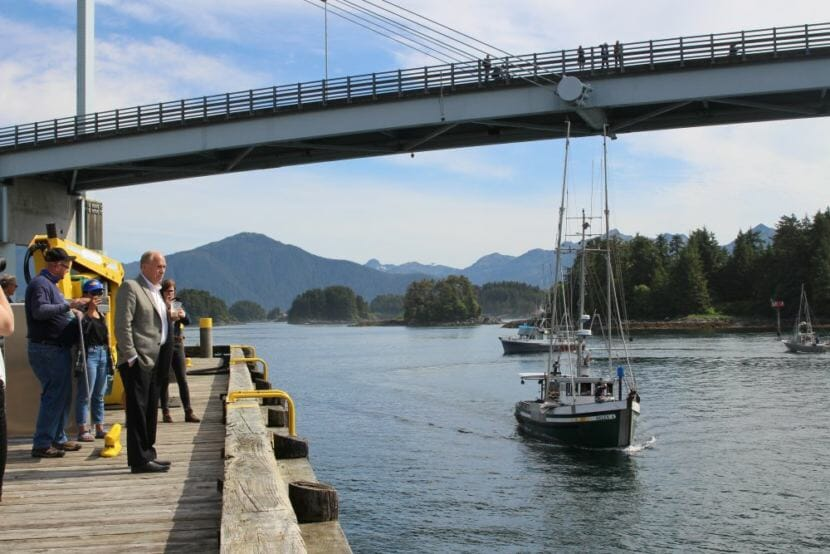 Alaska Gov. Bill Walker looks out over Sitka Sound, as trollers pass by calling for him to not sign a Pacific Salmon Treaty that would further cut Alaska's allocation. The salmon fleet organized a boat parade and rally to send that message. (Photo by Emily Kwong/KCAW)
