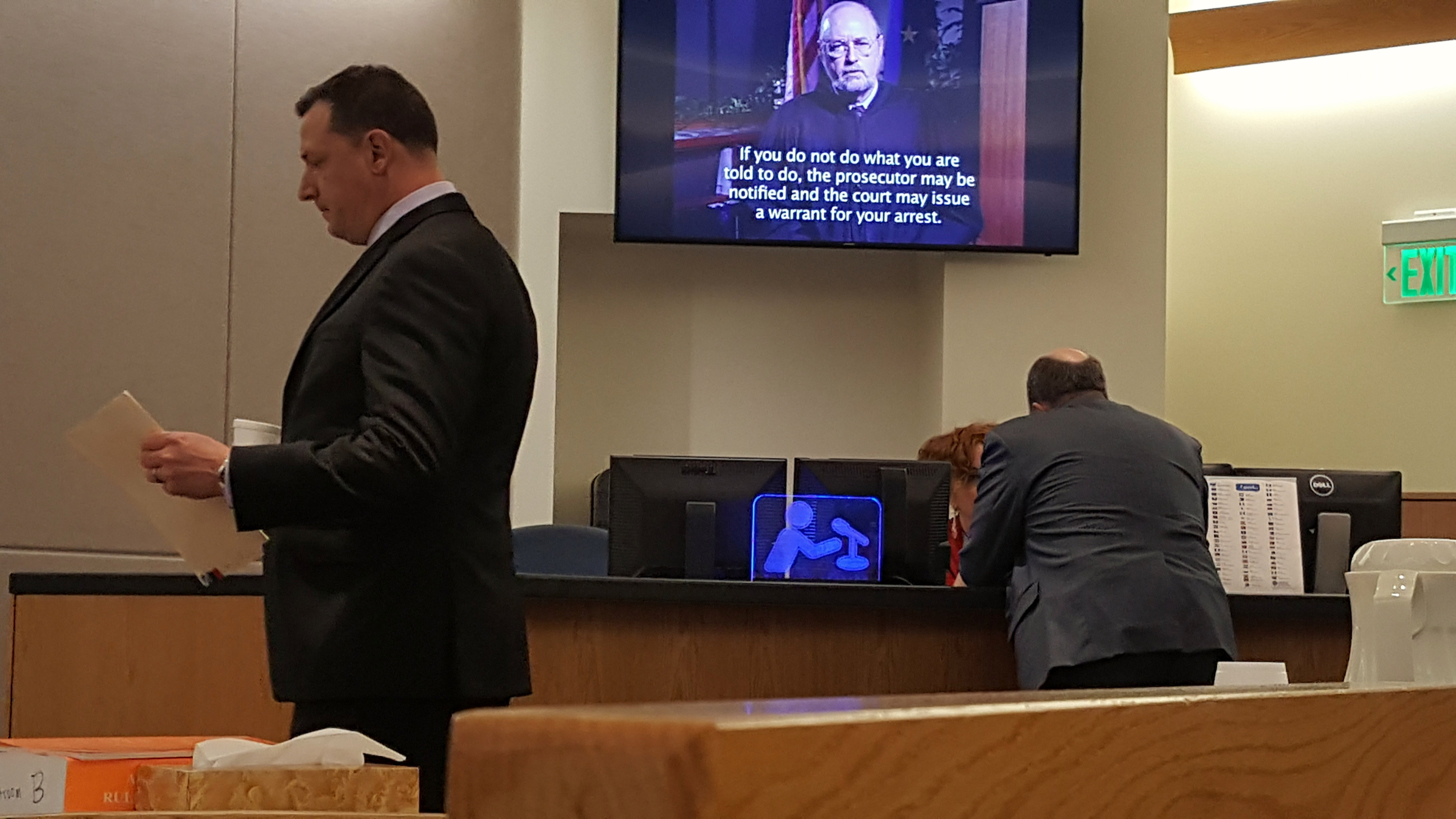 Chief Assistant Attorney General Paul Joseph Miovas looks over papers while Wallace Teflow talks with a Juneau District Court clerk before the arraignment of former Alaska Rep. Zachary Fansler on Thursday, June 21, 2018, on a charge of harassment. (Photo by Tripp J Crouse/KTOO)