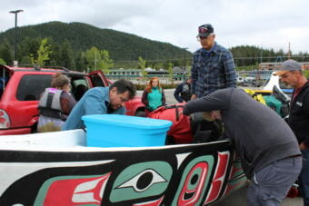 Dennis Jack, center, looks on as Doug Chilton, right, and other paddlers pack supplies into the Eagle canoe that veterans will paddle. May 29, 2018. q