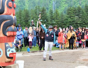 John Morris, a member of the Yanyeidí clan who once called the site home, raises his arm in triumph after helping to install the Gooch (wolf) totem pole. June 6, 2018. (Photo by Adelyn Baxter/KTOO)
