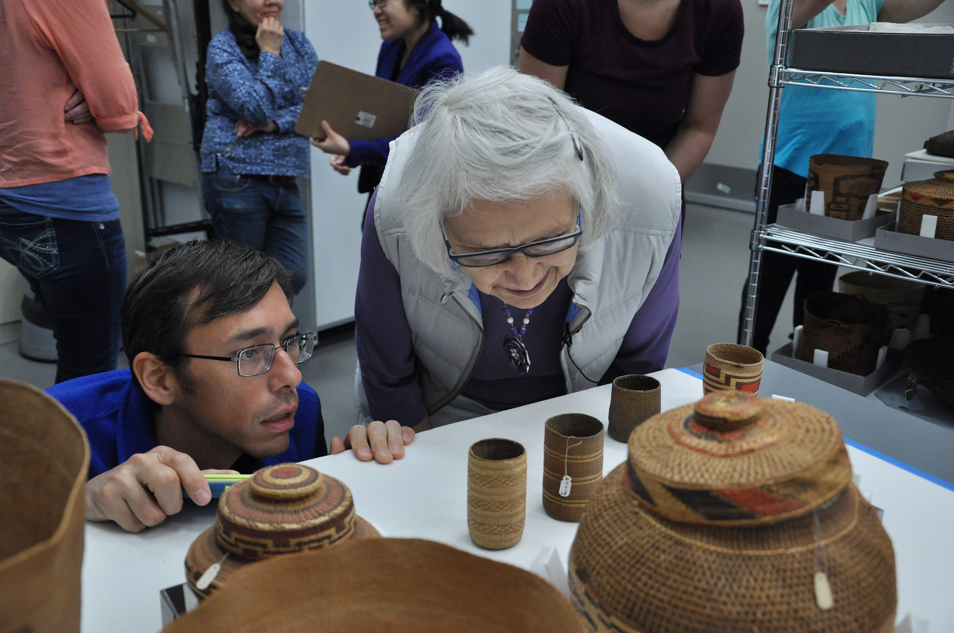 Hans Chester, left, of Sealaska Heritage Institute, and master Haida weaver Delores Churchill examine spruce root basketry in the collections vault of the Father Andrew P. Kashevaroff State Library, Archives and Museum in August 2017. (Photo by Davina Cole, courtesy Sealaska Heritage Institute)