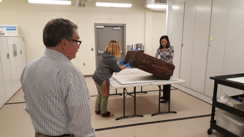 Sealaska Heritage Institute heritage director Chuck Smythe watches Monday, August 14, 2018, as collections manager Heather McClain and summer archives intern Miranda Worl set the bentwood box down to return to the collections. (Photo by Tripp J Crouse/KTOO)