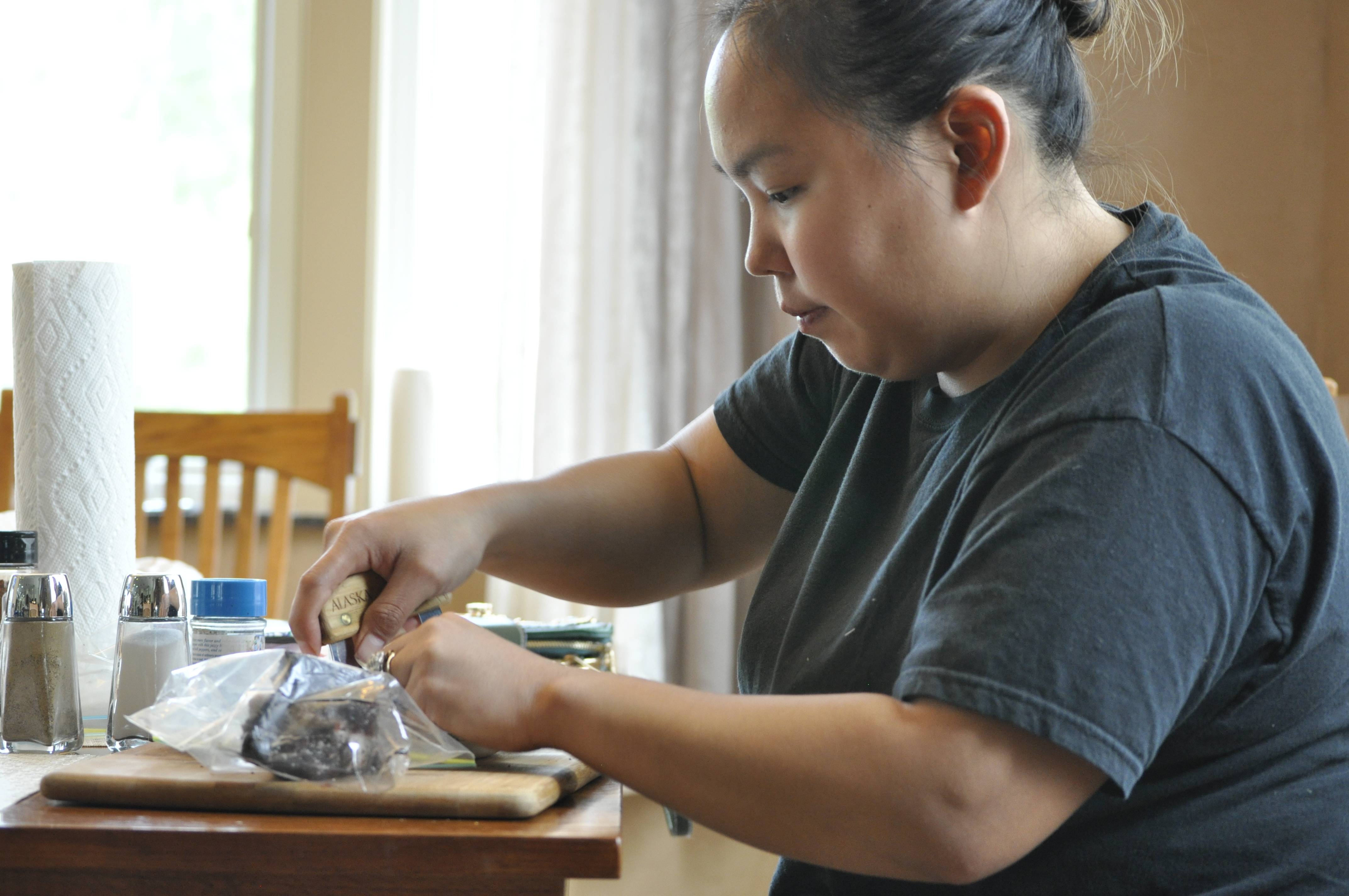 Alesha Tangman uses an ulu to cut up pieces of bowhead whale meat at her aunt and uncle's kitchen table in Wasilla. She uses Kunniak's spice mixtures on everything from salads to Maktak. (Photo by Erin McKinstry/Alaska Public Media)