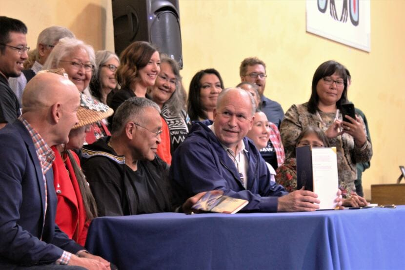 Gov. Bill Walker holds up the signed Administrative Order 300 surrounded by Alaska Native language advocates. (Photo Adelyn Baxter/KTOO)