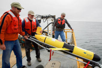 """Oregon State University oceanographer Jack Barth deploys a glider that will spend weeks at sea collecting data on everything from dissolved oxygen levels to temperature. """"When we used to think about hypoxia in the ocean, we think about little areas. But now what we're looking at is...out in the ocean, there's low oxygen...all along the coast,"""" he says. (Photo by Kristian Foden-Vencil/NPR)"""
