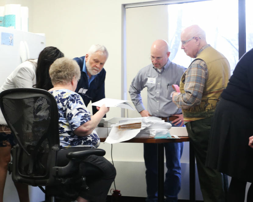 Official observers representing House District 1 candidates Bart LeBon and Kathryn Dodge watch the recount process at the Alaska Division of Elections office in Juneau on Nov. 30, 2018.