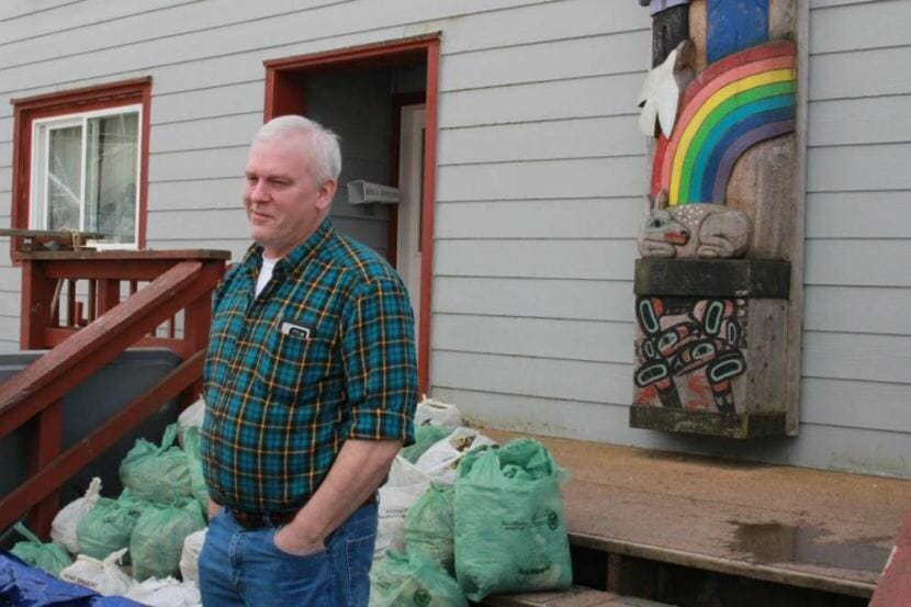 Jeff Feldpausch stands in front of bags of hemlock branches, ready for distribution to elders. He noted the bare spots on the branches, illustrating the annual need for subsistence coming up short.