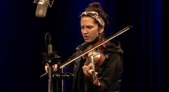 A picture of a woman playing a violin and singing into a microphone.
