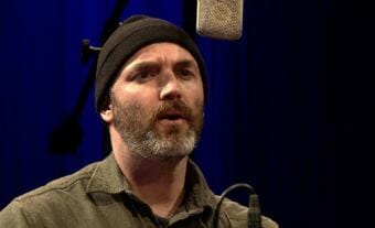 An image of a man in a black hat singing into a microphone. A video still of Seattle songwriter and guitarist Eli West performing a Red Carpet Concert at KTOO Public Media during the 2018 Alaska Folk Festival in Juneau.