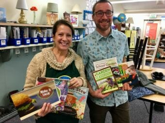 Karen Goodell and master gardener Joel Bos show off prizes from winning the Alaska DNR Farm to School Challenge, on Dec. 4, 2018. (Photo by Zoe Grueskin/KTOO)