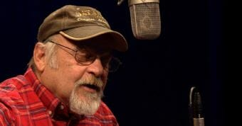 """Picture of man singing into microphone. Longtime Juneau musician Mike Truax performs his song """"It's Me"""" for a Red Carpet Concert during the 2018 Alaska Folk Festival at KTOO in Juneau. (Screen capture image from video https://www.youtube.com/embed/vpuxQATosZ0 )"""