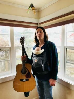 A picture of a man holding a guitar with a baby carrier on his chest. KTOO volunteer DJ Patrick Klacza hosts the radio show Cat Plaza on KXLL 100.7 FM Juneau. (Image courtesy of the artist)