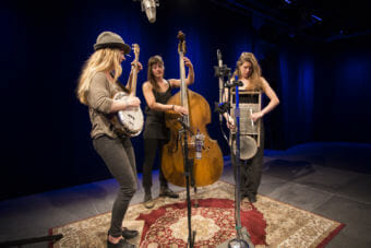 Three women stand around a microphone playing upright bass, washboard and banjo. Alaska band Damn Fantasies and the Could Be Possibilities perform a Red Carpet Concert at KTOO Public Media on April 12, 2018. (Photo by Annie Bartholomew/KTOO)