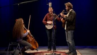 An image of a woman playing cello, a woman playing banjo and a man playing guitar on a stage around a microphone. A video still of the Anchorage folk group String of Lights performing a Red Carpet Concert at KTOO Public Media during the 2018 Alaska Folk Festival.