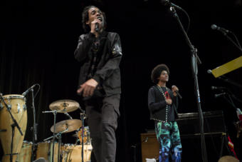 """Two men rap into microphones on stage Juneau hip hop duo Chris Talley and Arias Hoyle opened for Khu.éex' at Centennial Hall on Monday, January 28, 2019. The duo released a video for their song """"Zibit"""" in November which honors southeast Alaska's history and culture. (Photo by Annie Bartholomew/KTOO)"""