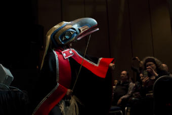 A man in a button blanket and raven mask looks into light at Centennial Hall. Gene Tagaban dances with Khu.éex' at Centennial Hall on Monday, January 28, 2019. Tagaban played flute and sang as part of the performance. (Photo by Annie Bartholomew/KTOO)