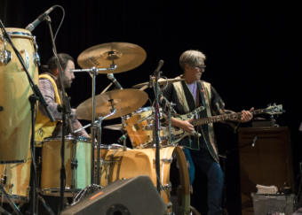 A man plays bass while another man plays on a drum kit. Tlingit glass artist and founding member of the band Khu.éex' Preston Singletary plays bass at Centennial Hall with Sitka percussionist Ed Littlefield on drums, Monday, January 28, 2019. (Photo by Annie Bartholomew/KTOO)