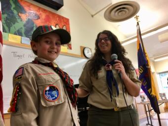 """Kelsie Powers (left) receives her Arrow of Light, the highest award a Cub Scout can earn, at a pack meeting on April 20, 2019. Her den leader, Emily Lockie (right) presented the award. Of Kelsie, she said, """"She's a great leader, she's empathetic, and she's so good at standing up for what is right."""" (Photo by Zoe Grueskin/KTOO)"""