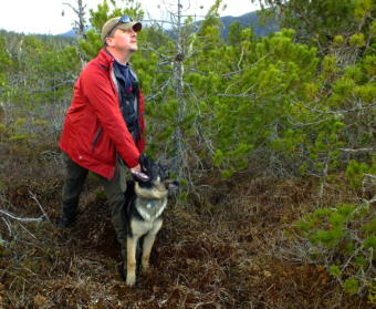 """SEADOGS' Liam Higgins holds on to Oskar, his 5 month old German Shepherd, while he looks to make sure that a volunteer is hidden before giving the command to """"Find him!"""". (Photo by Matt Miller/KTOO)"""