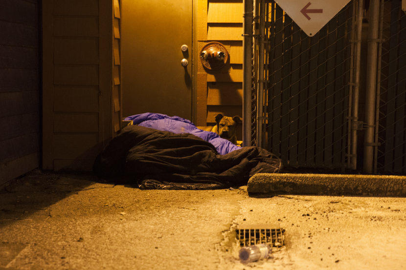 Two people and a dog curl up near a boiler room on Shattuck Way on Jan. 20, 2017 in downtown Juneau, Alaska. (Photo by Rashah McChesney/Alaska's Energy Desk)