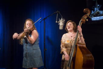 A woman plays violin while another woman playing upright bass sings into a microphone in a television studio.Katie Klan and Angela Brock of the Homer band Burnt Down House perform a Red Carpet Concert at KTOO Public Media during the 2019 Alaska Folk Festival. (Photo by Annie Bartholomew/KTOO)