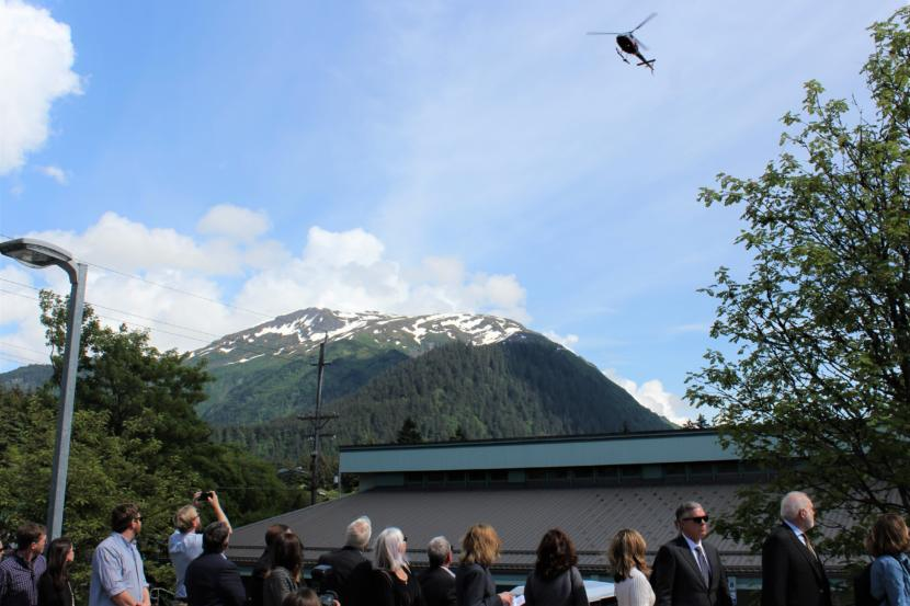 A helicopter flies over the memorial service for three air ambulance crew members who died when their plane went down in January. (Photo by Adelyn Baxter/KTOO)