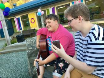 """Callum Marks (right) serves as a """"modern day page turner"""" for Theo Houck, who played a set of queer love songs at Juneau's first youth Pride party on June 20, 2019. (Photo by Zoe Grueskin/KTOO)"""