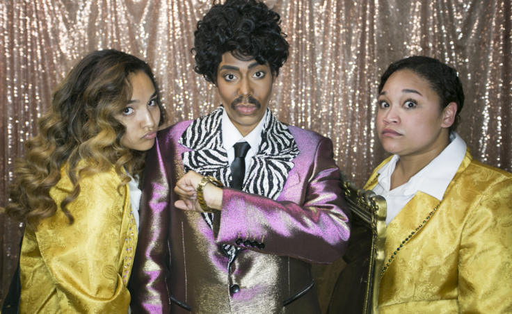"Two women in smoking jacket tuxedos flank a drag king in a zebra and purple metallic suit backstage. Drag king and clothing designer Tahir McInnes who performs as the drag persona ""Tyquan"" danced to a routine inspired by Morris Day and The Time from the Prince film 'Purple Rain.' McInnis was supported by dancers Honour Miller-Austin and Salissa Thole at Centennial Hall for the 5th Annual GLITZ Drag Show and Juneau Pride Kickoff on Friday, June 14, 2019. (Photo by Annie Bartholomew/KTOO)"