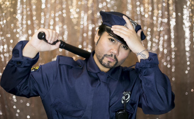 "A drag king with a baton poses backstage as a police officer. Juneau artist Christianne Carrillo who performs as the drag king ""Will Duja"" poses backstage as police officers at Centennial Hall for the 5th Annual GLITZ Drag Show and Juneau Pride Kickoff at Centennial Hall on Friday, June 14, 2019. (Photo by Annie Bartholomew/KTOO)"