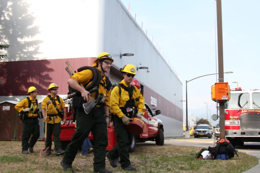 Wildland firefighters prepare to head into the woods in East Anchorage on Tuesday, July 2, 2019, to fight a fire that forced evacuations of a trailer park and two other areas of the city.