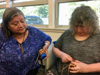 Holly Churchill (left) looks on as Brita Steinberger works on a basket during a Sealaska Heritage Institute seminar for teachers on Northwest Coast arts and math on Aug. 8, 2019. (Photo by Zoe Grueskin/KTOO)
