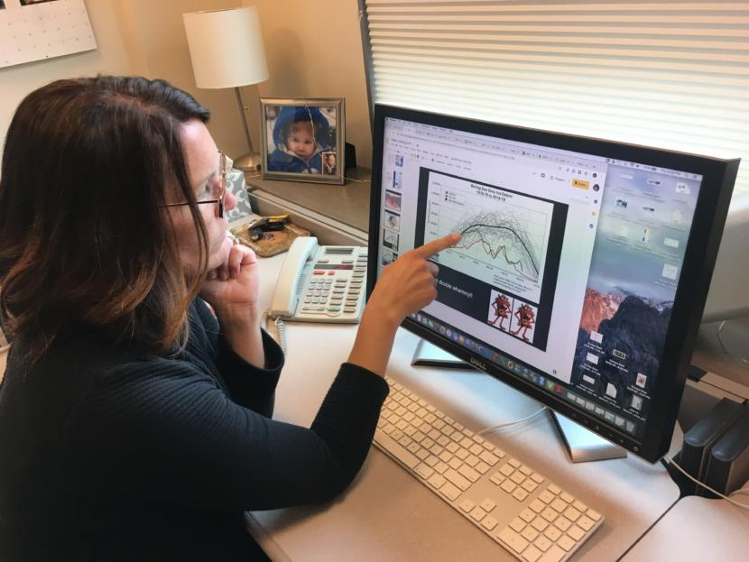 """Elizabeth Siddon, photographed in her office on Aug. 1, 2019, points to a figure charting sea ice extent in the Bering Sea, which shows a """"double whammy"""" of back-to-back low sea ice winters in 2017-18 and 2018-19. (Photo by Zoe Grueskin/KTOO)"""