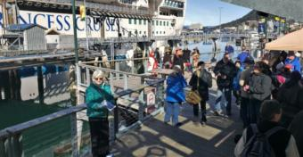 Vicki Logan of Travel Juneau greets and hands out walking maps to passengers of the Ruby Princess at the Franklin Dock on Sunday, April 28, 2019. (Photo by Jeremy Hsieh/KTOO)