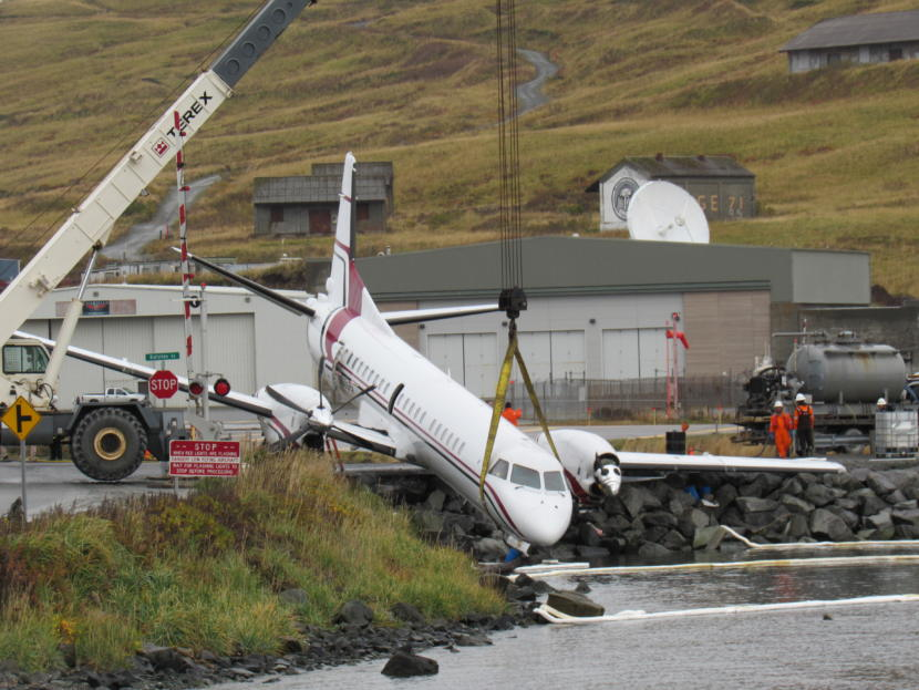 A crane hoists PenAir's Saab 2000 airplane on Oct. 18, 2019. One person was killed and multiple people were injured when the plane went off the runway while attempting to land the evening before.