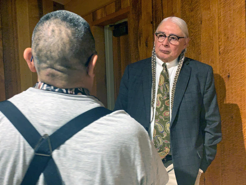 Walter Echo-Hawk talks to a man after giving a speech on the 1955 Tee-Hit-Ton Tlingit loss of a Supreme Court case on November 8, 2019, in Juneau, Alaska. (Photo by Rashah McChesney/Alaska's Energy Desk)