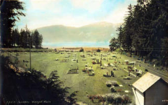This hand-tinted photograph shows a cemetery in Wrangell circa 1930.