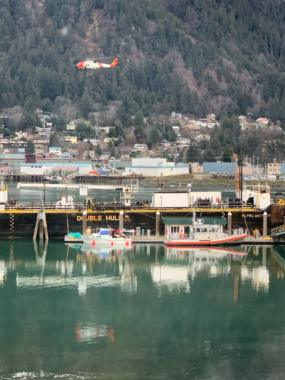 A Coast Guard Jayhawk helicopter flies over Gastineau Channel in Juneau as authorities investigate a pleasurecraft that had been reported unmanned and adrift with its motor running on Friday, Nov. 29, 2019. The Coast Guard later reached the vessel's owner and someone entrusted to move it and called off the search.