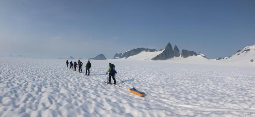 Juneau Icefield Research Program (JIRP) students during a four day and 83 kilometer ski traverse across Taku Glacier in 2019, carrying all their food, water, clothing, tents, and science gear as they help measure the mass balance along the way. (Photo courtesy of Christopher McNeil/USGS)