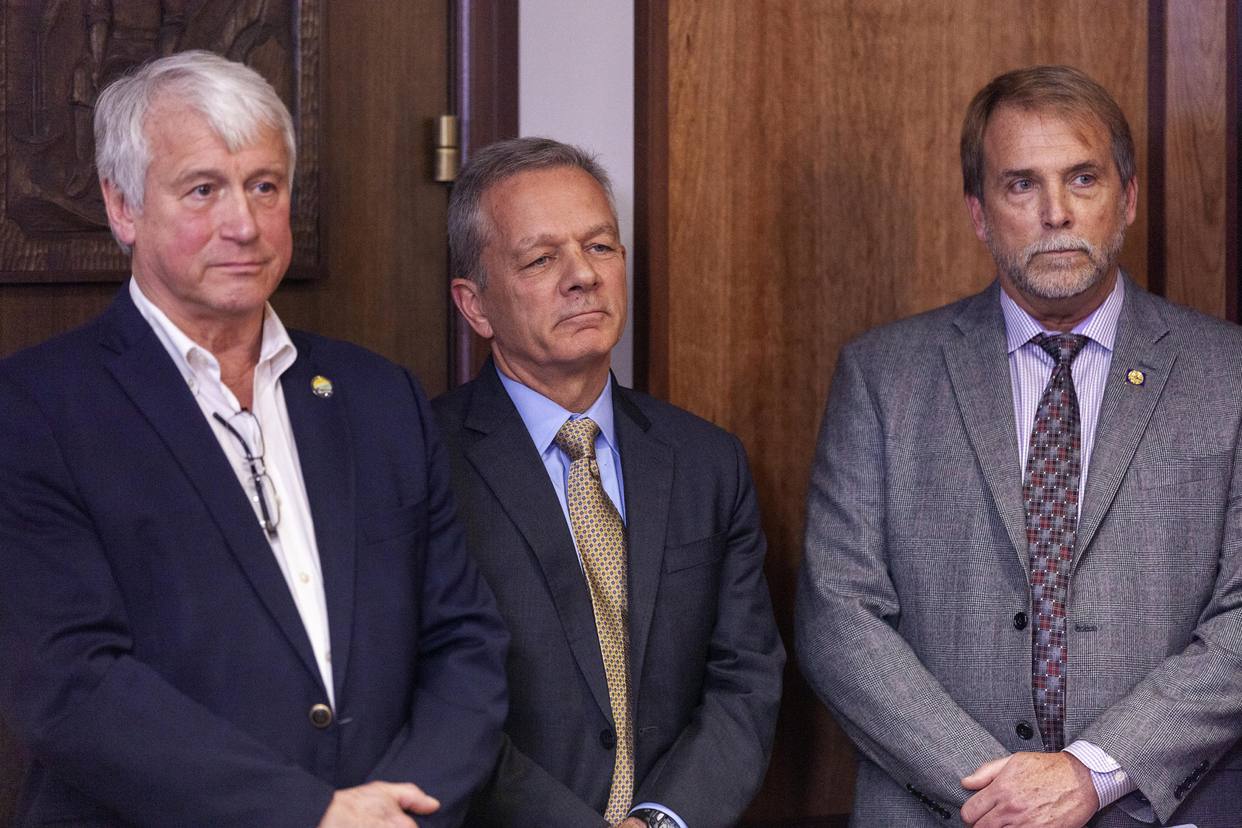 Department of Transportation and Public Facilities Commissioner John MacKinnon, Gov. Mike Dunleavy's Chief of Staff Ben Stevens, and Senior Policy Advisor Brett Huber watch a press conference unveiling Dunleavy's budget proposal on Wednesday, December 11, 2019, at the Capitol in Juneau, Alaska. (Photo by Rashah McChesney/KTOO)