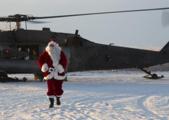 A man dressed as Santa Claus walks out of a Black Hawk helicopter.
