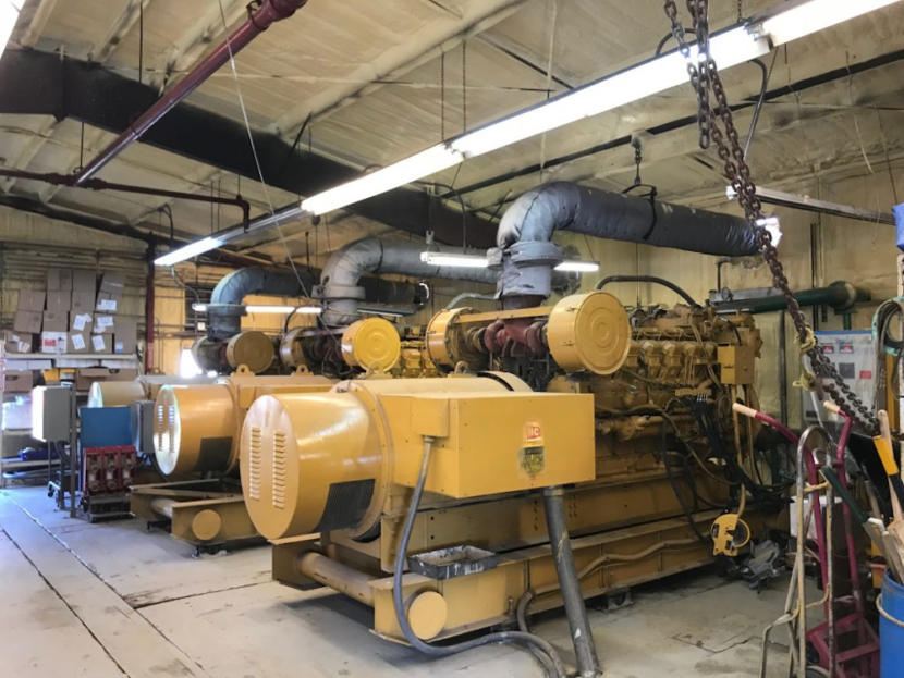 Two large diesel generators, painted yellow and sitting in a warehouse-style facility.