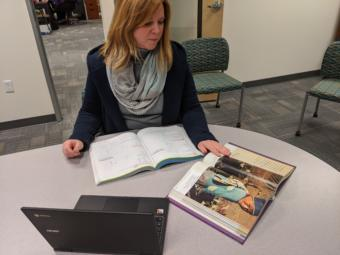 Jennifer Knutson, the senior director of teaching and learning for the Anchorage School District, shows some textbooks and a district-issue Chromebook that students have access to on March 13, 2020. She says that there will need to be a combination of traditional and e-learning opportunities for students during school closure. (Photo by Mayowa Aina/Alaska Public Media)
